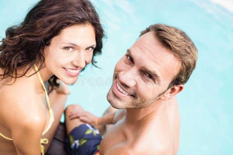 Nahaufnahme von den jungen Paaren, die durch Poolside sitzen stockfoto