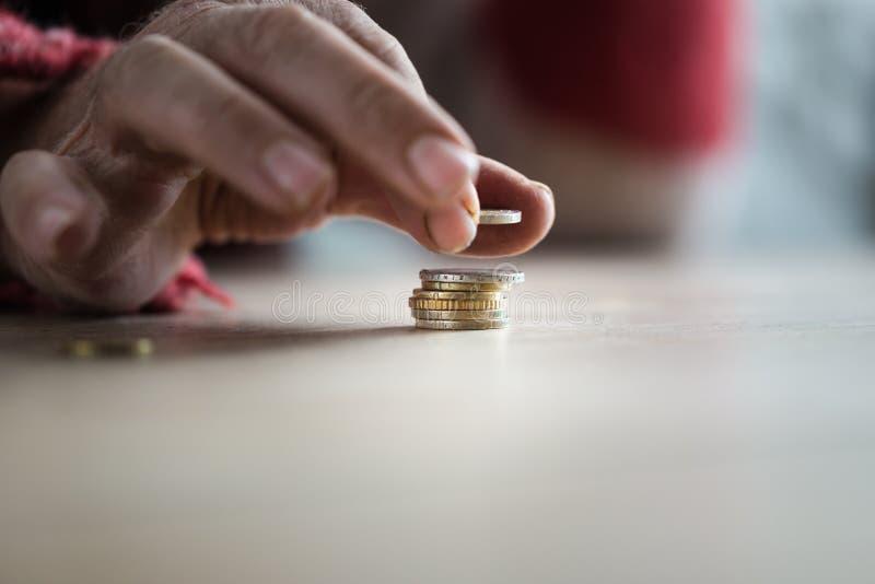 Nahaufnahme von den männlichen älteren Händen, die Euromünzen stapeln lizenzfreie stockfotografie