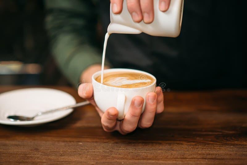 Nahaufnahme von den männlichen Händen, die Creme Kaffee hinzufügen stockbild