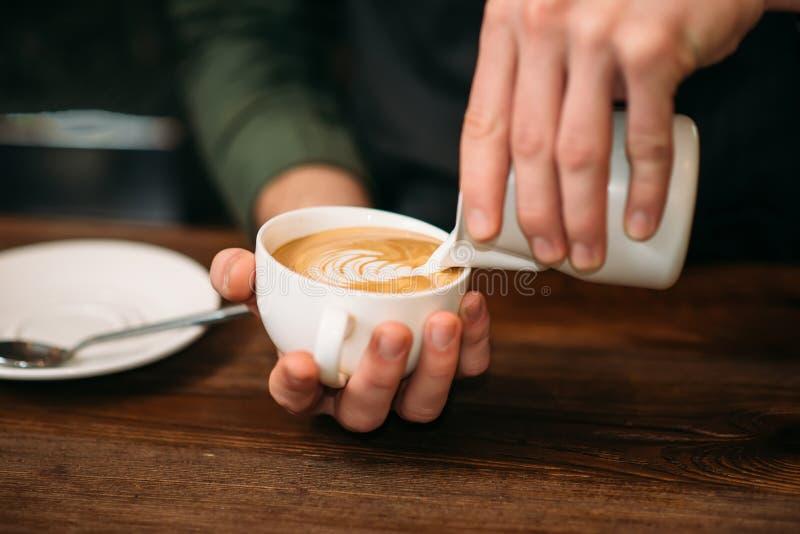Nahaufnahme von den männlichen Händen, die Creme Kaffee hinzufügen lizenzfreies stockbild