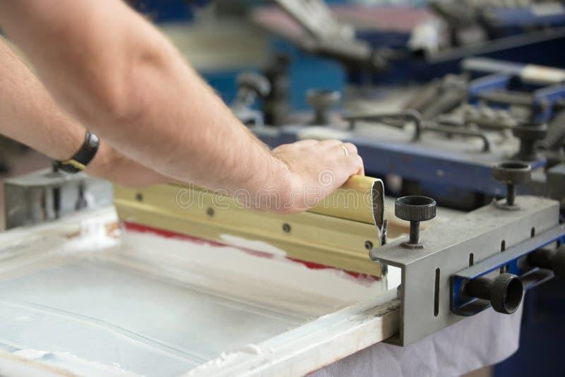 Nahaufnahme von den männlichen Händen, die mit Gummiwalze arbeiten stockfoto