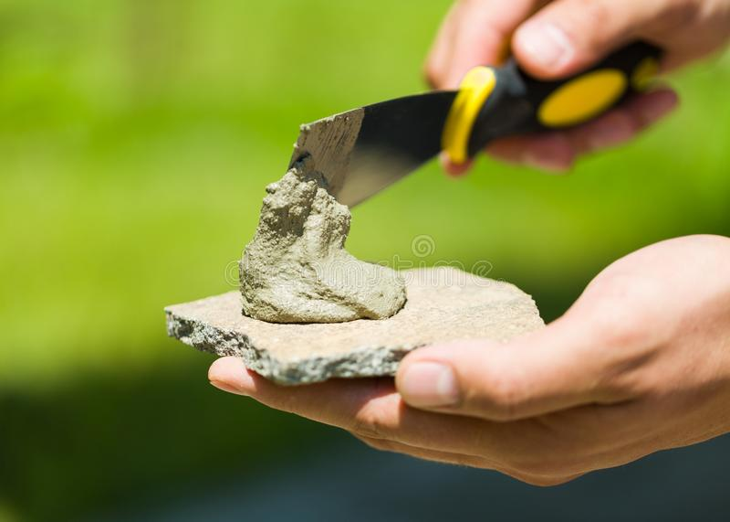 Nahaufnahme von den männlichen Händen, die Steinbruchstein schmieren stockfotografie