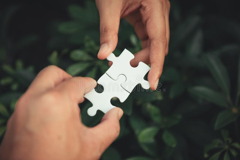 Nahaufnahme von den Mann- und Frauenhänden, die zusammen Puzzlen anschließen stockfoto