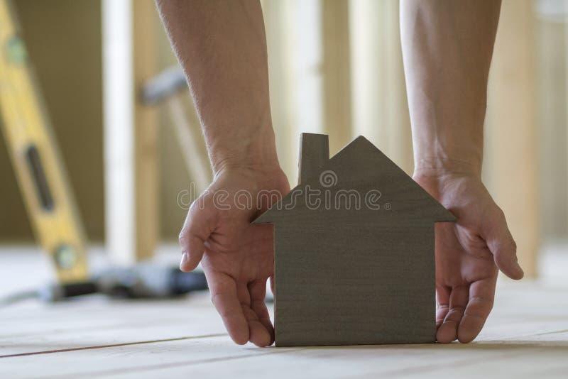 Nahaufnahme von den muskulösen männlichen Händen, die kleines braunes hölzernes Musterhaus auf unscharfem Hintergrund von Gebäude lizenzfreie stockbilder