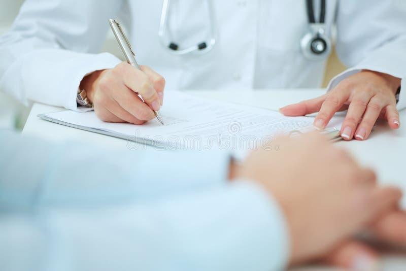 Nahaufnahme von den Patientenhänden und -doktor, die Kenntnisse nehmen stockfoto