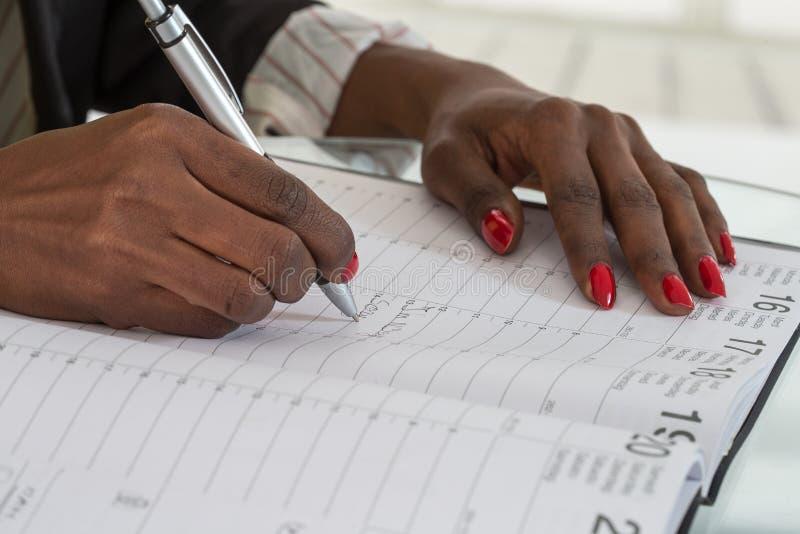 Nahaufnahme von den schwarzen Händen, die Zeitplan in Kalender-Tagebuch schreiben lizenzfreies stockbild