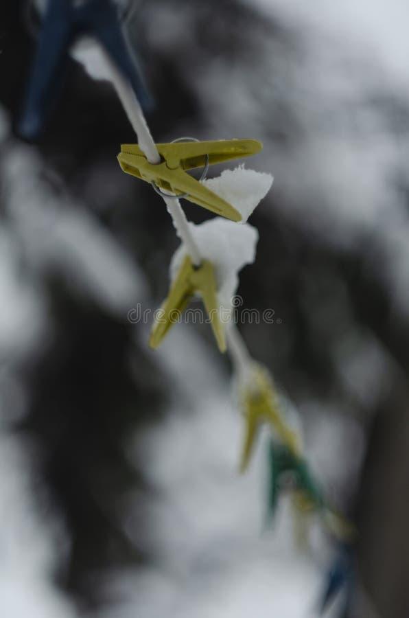 Nahaufnahme von den Wäscheklammern für waschende Kleidung, befestigt zu einem schneebedeckten Seil während drei Blizzarde und der lizenzfreies stockbild