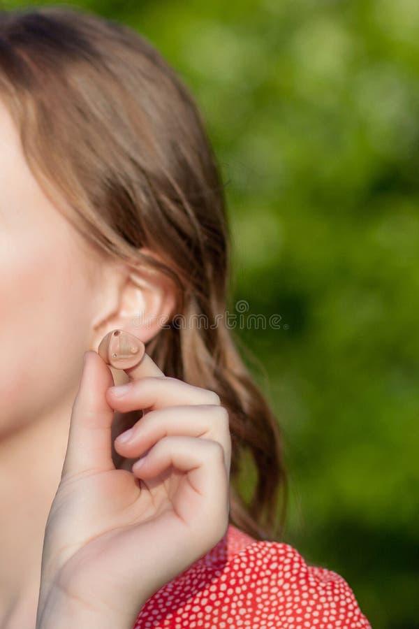 Nahaufnahme von den weiblichen Händen, die Hörgerät in Ohr einsetzen Modernes digitales im OhrHörgerät für Taubheit und das schwe lizenzfreie stockfotografie