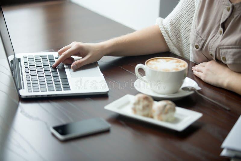 Nahaufnahme von den weiblichen Händen, die an Laptop im Café arbeiten lizenzfreies stockfoto