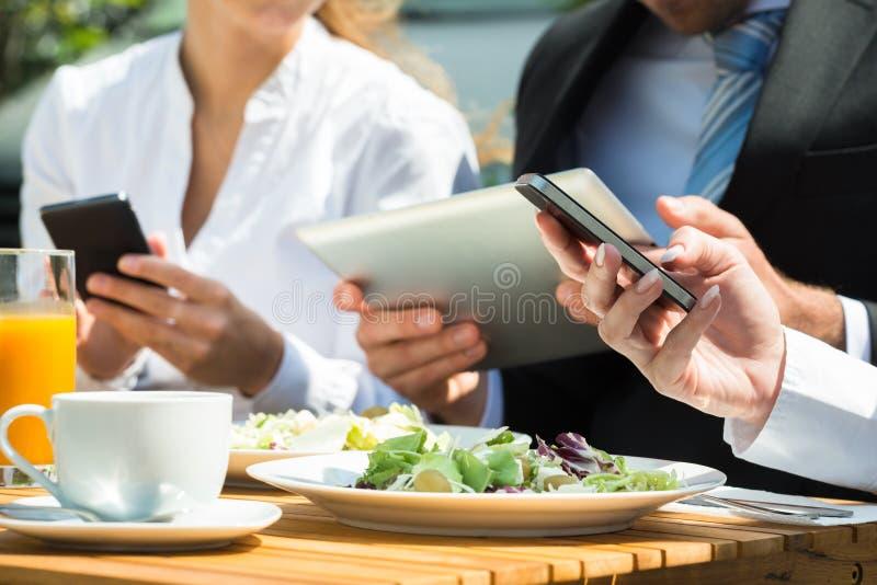 Nahaufnahme von den Wirtschaftlern, die Digital-Tablet und -Handy verwenden lizenzfreie stockbilder