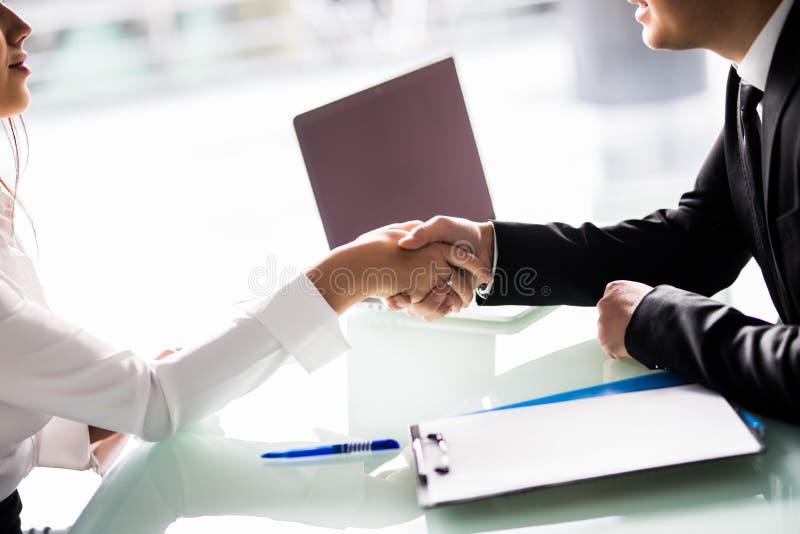 Nahaufnahme von den Wirtschaftlern, die Hände am Schreibtisch nach Zeichen des Vertrages rütteln lizenzfreie stockfotos