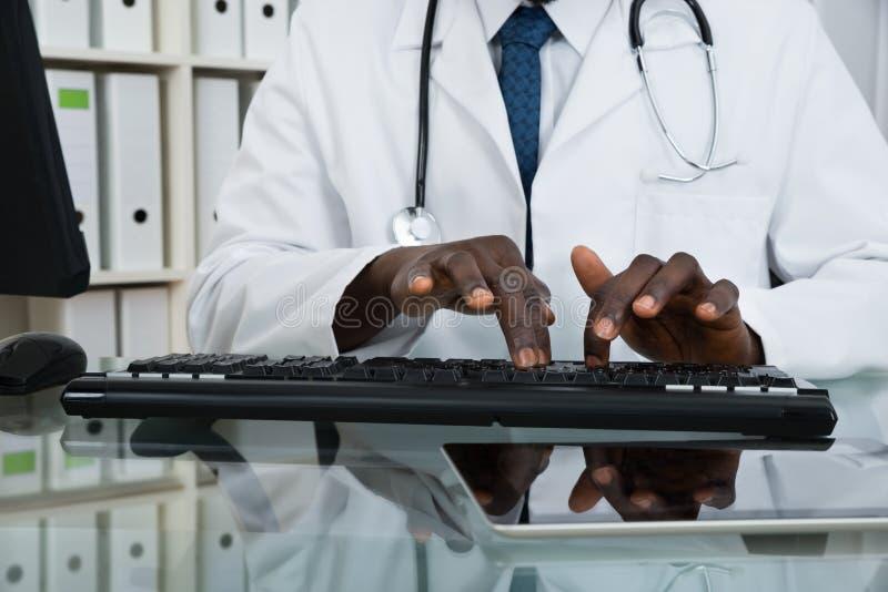 Nahaufnahme von Doktor Typing On Keyboard lizenzfreie stockbilder