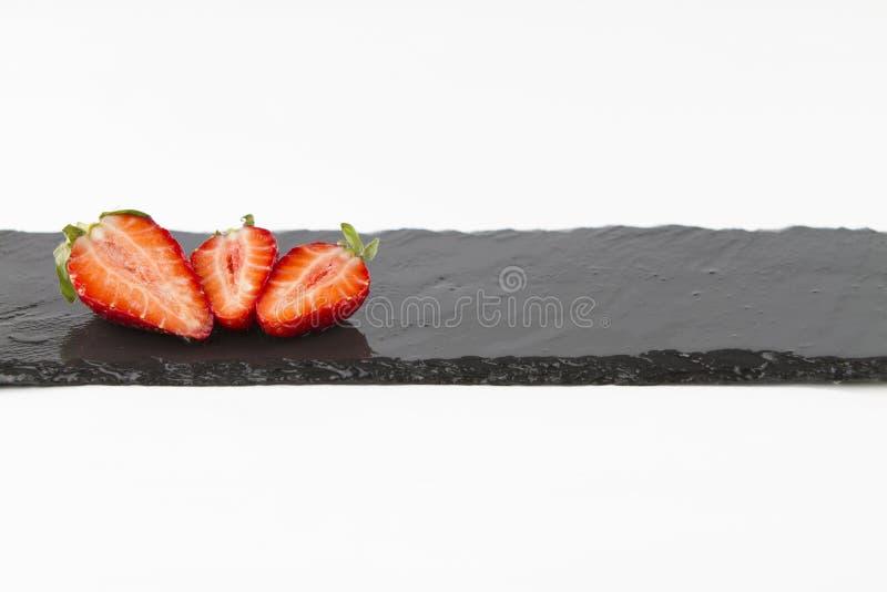 Nahaufnahme von drei Erdbeeren auf einem rechteckigen Streifen des nass Schiefers auf einem weißen Hintergrundschuß in der hohen  stockbilder