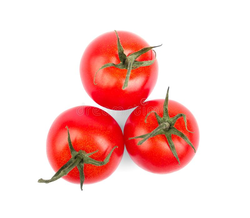 Nahaufnahme von drei hellen roten Tomaten mit den Blättern lokalisiert auf einem weißen Hintergrund Saftige und frische Tomaten G lizenzfreie stockfotografie