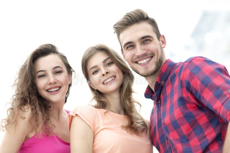 Nahaufnahme von drei jungen Leuten, die auf weißem Hintergrund lächeln stockfotografie