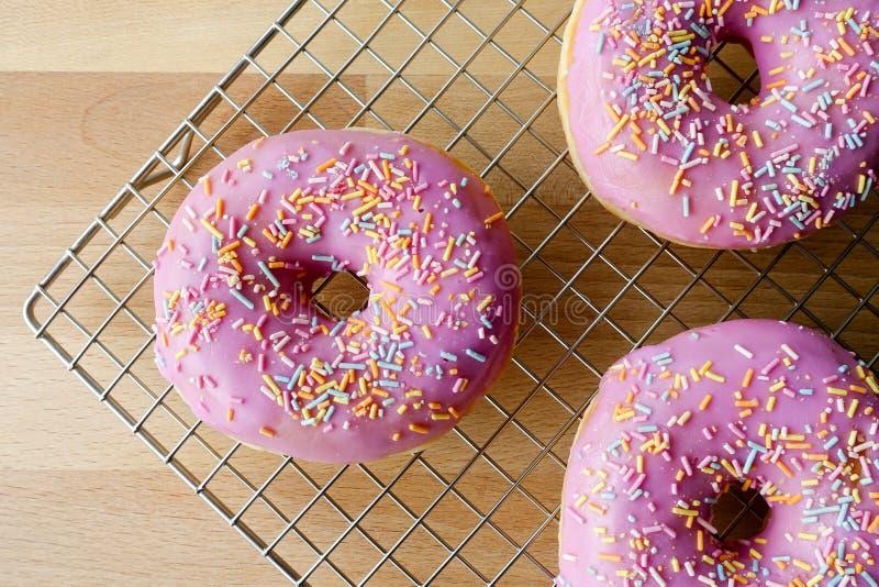 Nahaufnahme von drei rosa Donuts auf abkühlendem Gestell stockbild