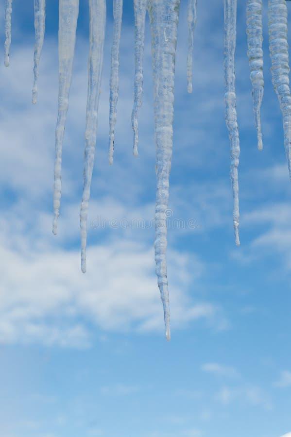 Nahaufnahme von Eiszapfen gegen einen blauen Himmel mit Wolken lizenzfreies stockfoto