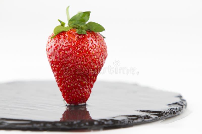 Nahaufnahme von Erdbeeren auf einer nass runden Schieferplatte auf einem weißen Hintergrundschuß in der hohen Winkelsicht mit sel stockfoto