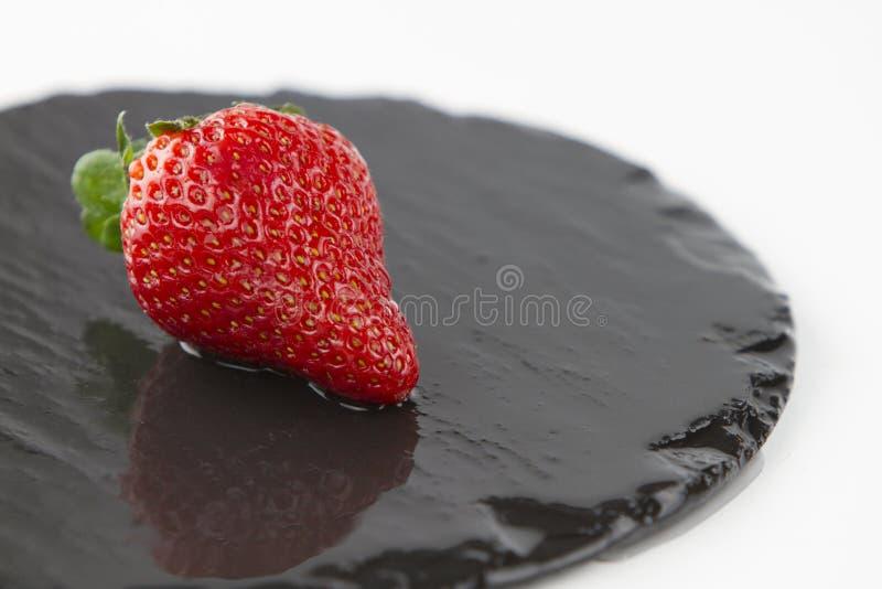Nahaufnahme von Erdbeeren auf einer nass runden Schieferplatte auf einem weißen Hintergrundschuß in der hohen Winkelsicht mit sel stockfotos