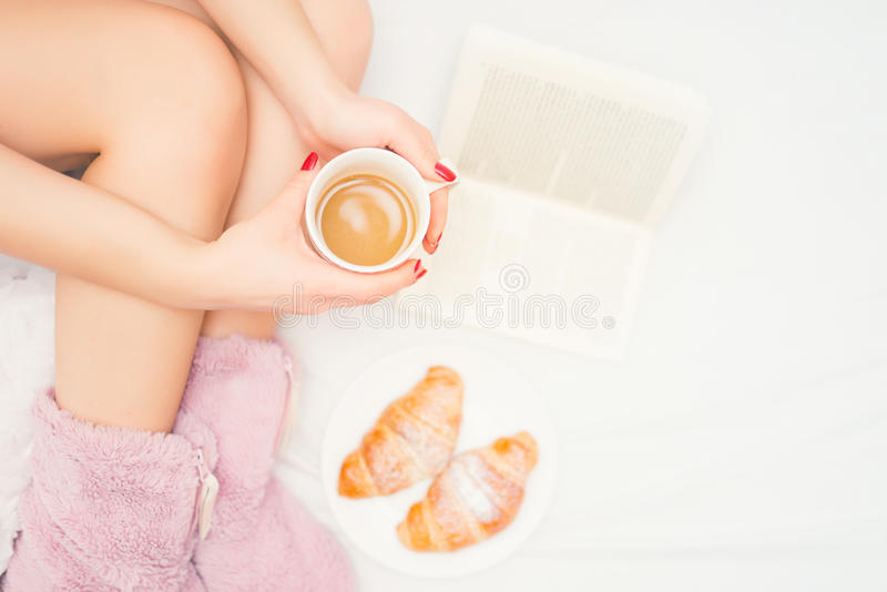 Nahaufnahme von Frauenbeinen mit den flaumigen Pantoffeln, die einen Kaffee trinken und ein gutes Buch lesen lizenzfreie stockfotografie