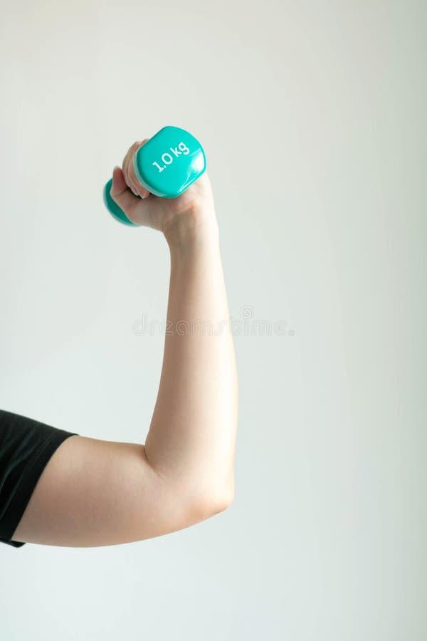 Nahaufnahme von Frauenhandanhebenden Dummköpfen wiegt 1 Kilogramm auf weißem Hintergrund stockfoto