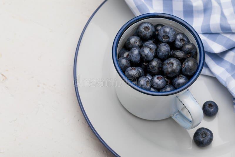 Nahaufnahme von frischen Blaubeeren in der weißen Porzellanschale stockfotografie