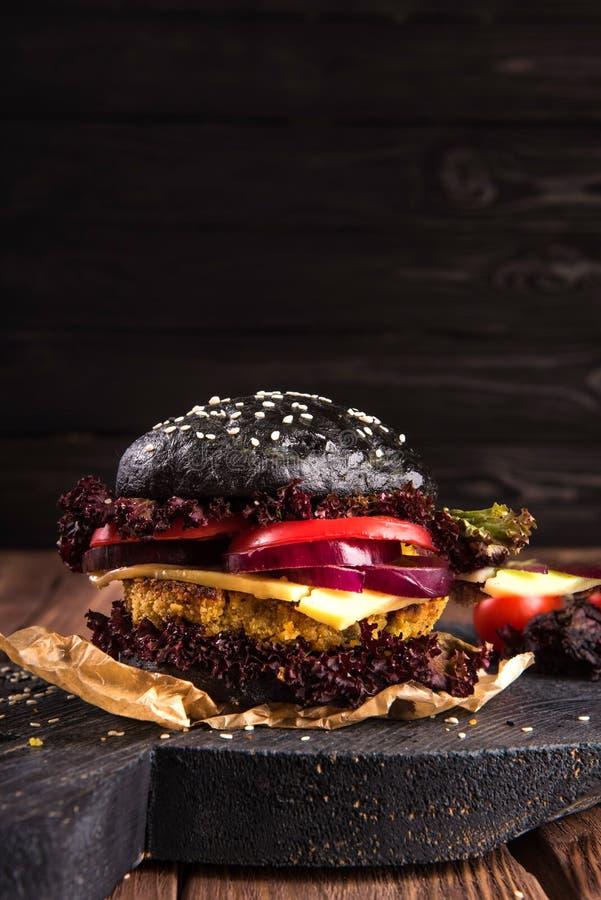 Nahaufnahme von gemachten Rindfleischhauptburgern mit Kopfsalat und Majonäse diente auf kleinem hölzernem Schneidebrett Dunkler H stockbilder