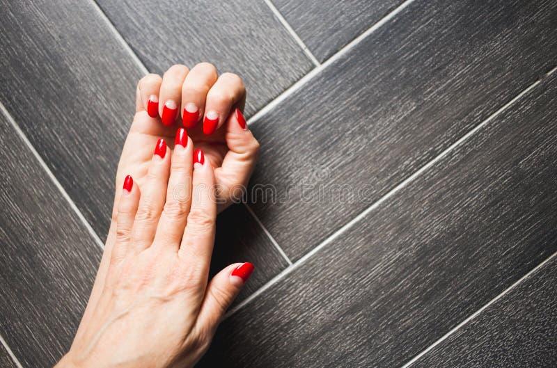 Nahaufnahme von Händen einer Frau mit dunkelroter Maniküre auf Nägeln gegen dunklen hölzernen Hintergrund lizenzfreie stockfotos