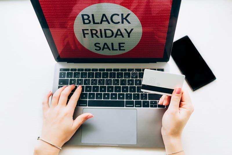 Nahaufnahme von Händen einer Frau mit Kreditkarteschwarzem Freitag bietet auf Laptop an auf weißem background stockfotos