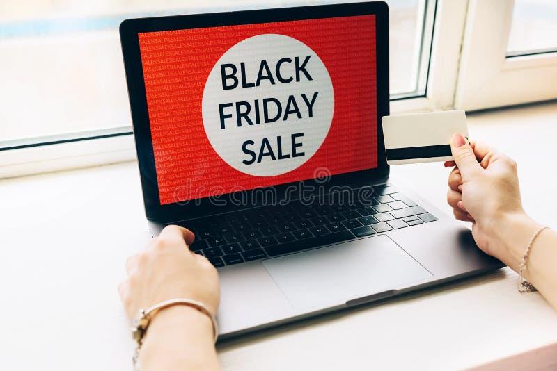 Nahaufnahme von Händen einer Frau mit Kreditkarteschwarzem Freitag bietet auf Laptop an auf weißem background lizenzfreies stockfoto