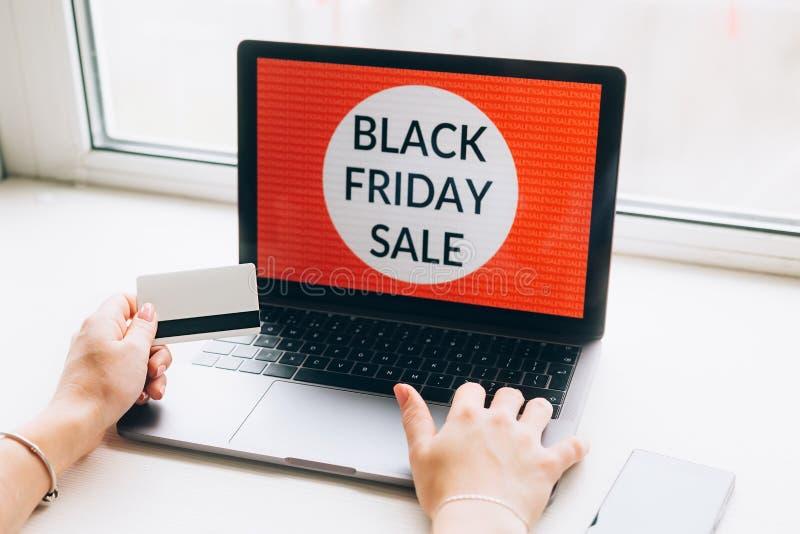 Nahaufnahme von Händen einer Frau mit Kreditkarteschwarzem Freitag bietet auf Laptop an auf weißem background stockbilder