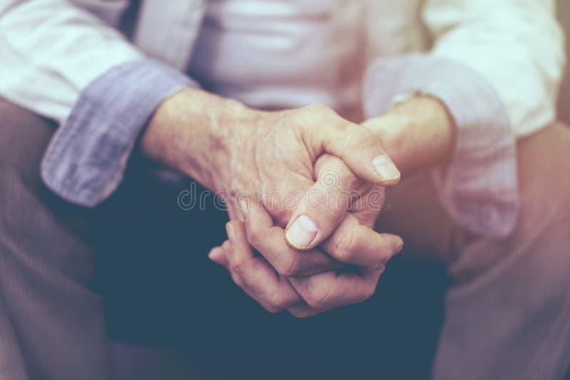 Nahaufnahme von Händen eines älteren Mannes umklammerte stockbild