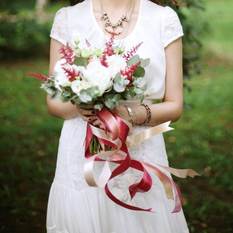 Nahaufnahme von Hochzeitsblumen mit Fliegenbändern lizenzfreie stockfotos