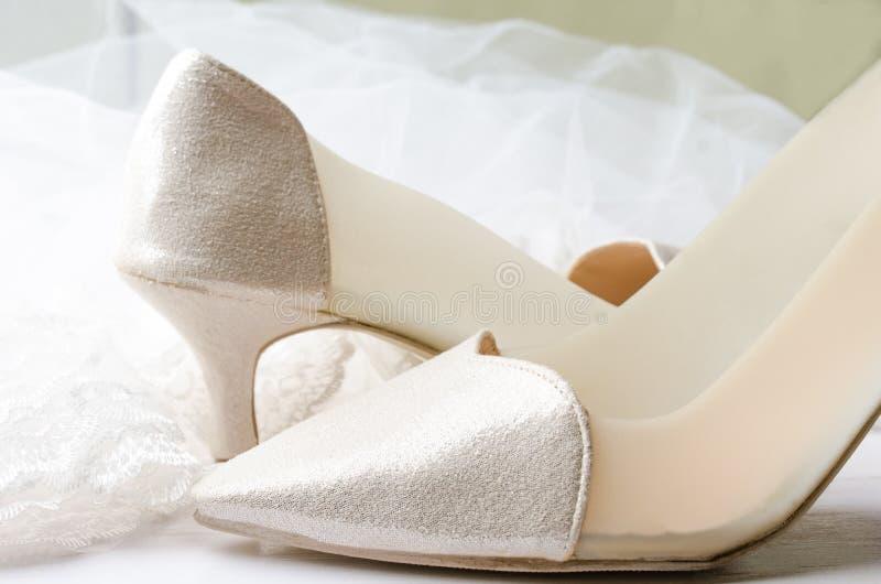 Nahaufnahme von Hochzeitsschuhen mit Spitzehochzeitsschleier auf weißem hölzernem stockfotos