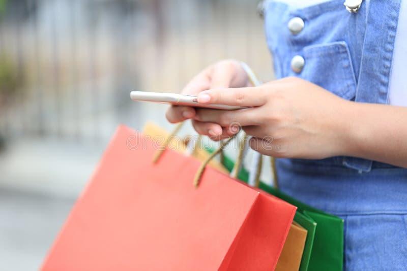 Nahaufnahme von Holdingsmartphone und -Einkaufstaschen der jungen Frau Handmit Stellung am AutoParkplatz stockbilder