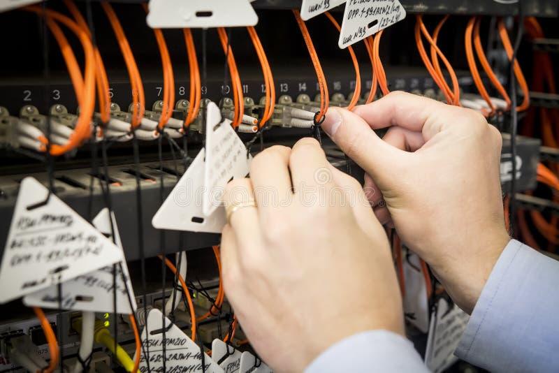 Nahaufnahme von Ingenieur ` s Hand mit optischem Verbindungskabel wird an Schalter angeschlossen AufstellungsRechenzentrumausrüst lizenzfreie stockfotografie