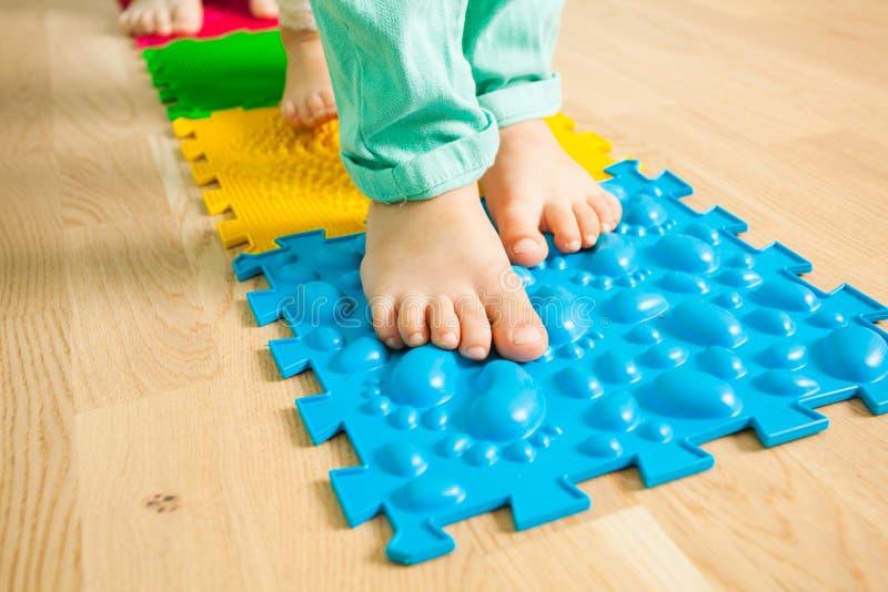 Nahaufnahme von Kinderfüßen bei der Stellung auf spezieller massierender Matte lizenzfreies stockfoto