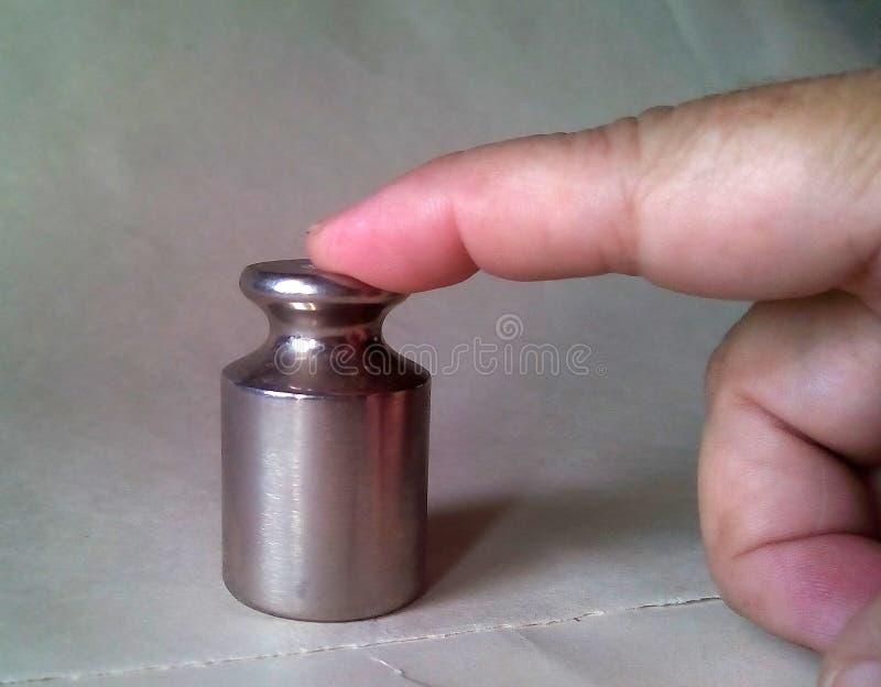 Nahaufnahme von kleinen Metallgewichten für Skalen, auf denen mit dem Zeigefinger gedrückt wird stockfotos