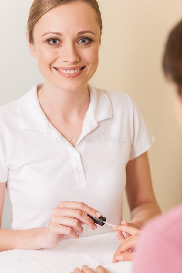 Nahaufnahme von Kosmetikerhandmalereinägeln der Frau im Salon stockfoto