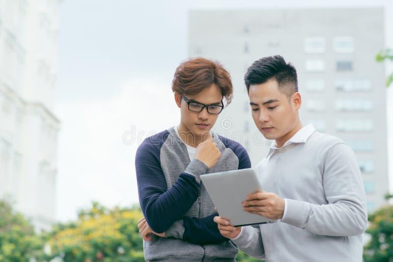 Nahaufnahme von lächelnden Mitarbeitern unter Verwendung des Tablets außerhalb - des Bildes lizenzfreies stockfoto