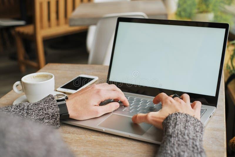 Nahaufnahme von männlichen Händen unter Verwendung des modernen Laptops zu Hause oder des Caféinnenraums, junger Berufsgeschäftsm stockbild