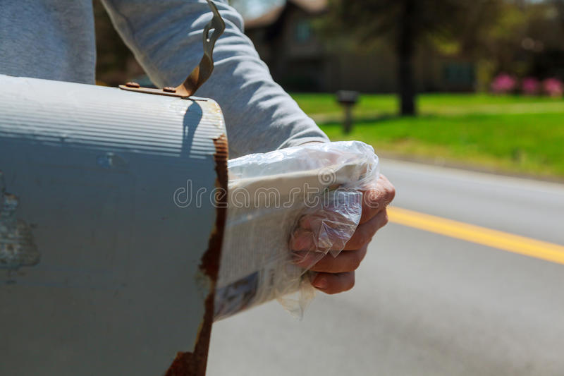 Nahaufnahme von Man& x27; s-Hand, die Brief vom Briefkasten außerhalb des Hauses nimmt stockbild