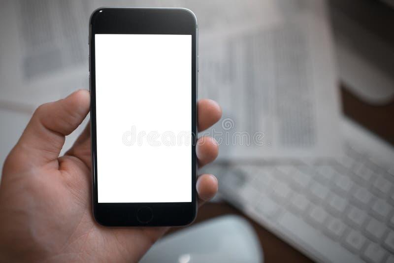 Nahaufnahme von Mannhandholding Smartphone mit leerem Modell auf Papierhintergrund stockbilder