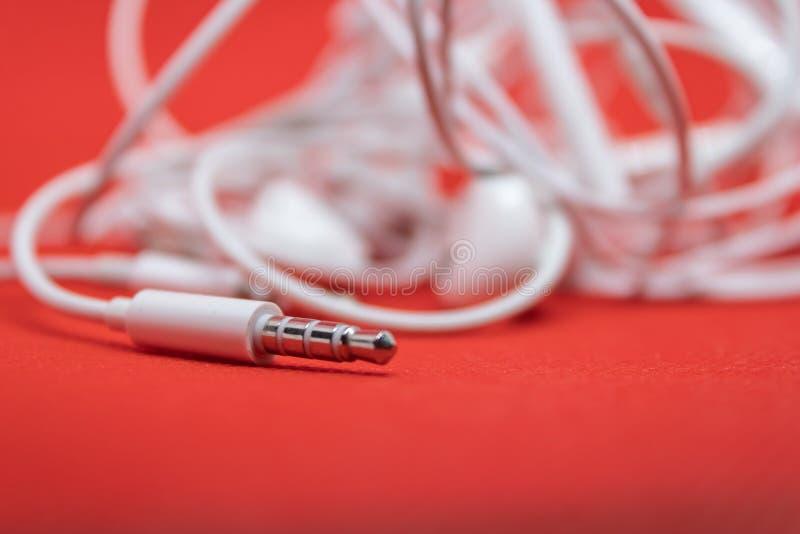 Nahaufnahme von 3 5 Millimeter-Inputstecker von den Kopfhörern kompatibel mit Spielern mp3 und Telefonen auf dem roten Hintergrun lizenzfreie stockfotos