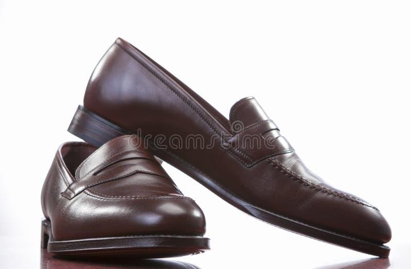 Nahaufnahme von Paaren von stilvollem Brown Penny Loafer Shoes Against White stockfotografie