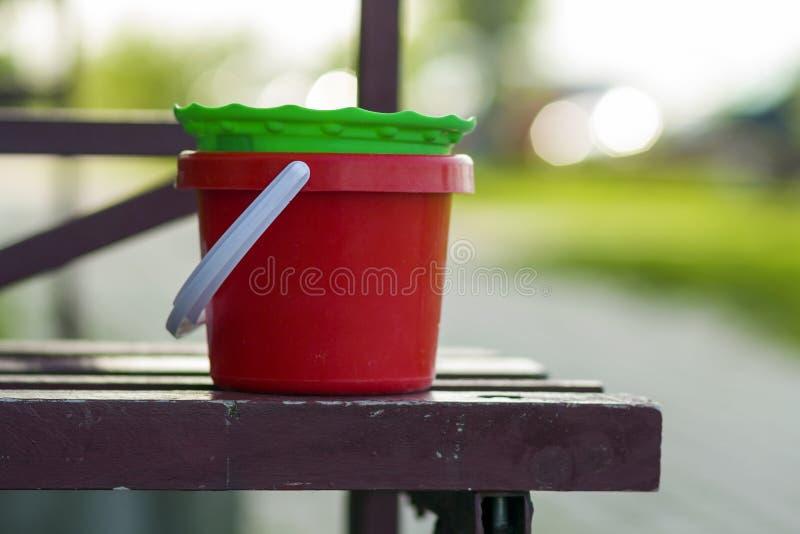 Nahaufnahme von Plastikroten und grünen Eimern des babyspielzeugs auf alter brauner Holzbank auf unscharfem hellem Sommer bokeh H stockfotografie