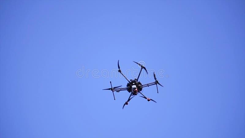 Nahaufnahme von quadcopter fliegend in Himmel clip Großes quadcopter mit den leistungsfähigen Motoren, die auf blauen Himmel des  lizenzfreies stockfoto