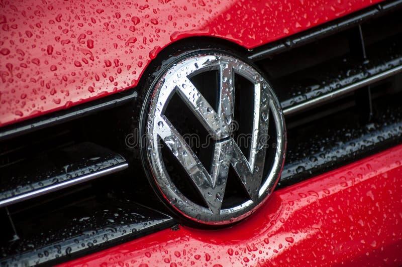 Nahaufnahme von Regentropfen auf rotem VW Polo Logo auf der Autofront geparkt der Straße lizenzfreie stockfotografie