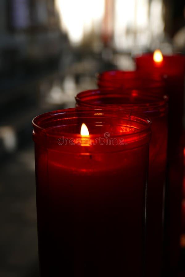 Nahaufnahme von roten Kerzen in einer Kirche lizenzfreie stockbilder