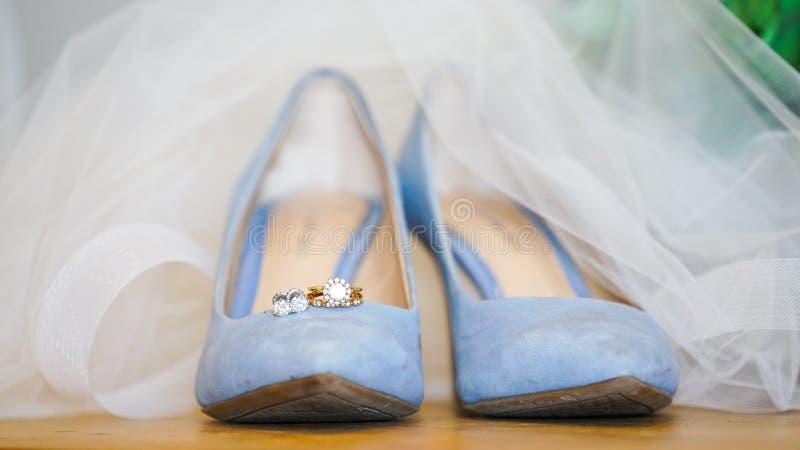 Nahaufnahme von schönen hellblauen weiblichen Heiratsschuhen unter einem weißen Heiratskleid lizenzfreie stockfotos